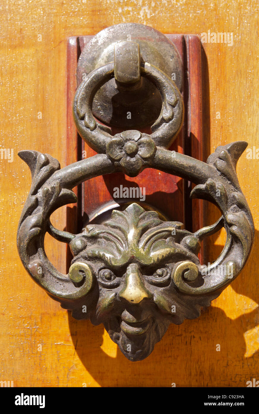 An Ornate Door Knocker In The Shape Of A Human Face, With A Wicked  Expression, On A Door In The Town Of Mosta.