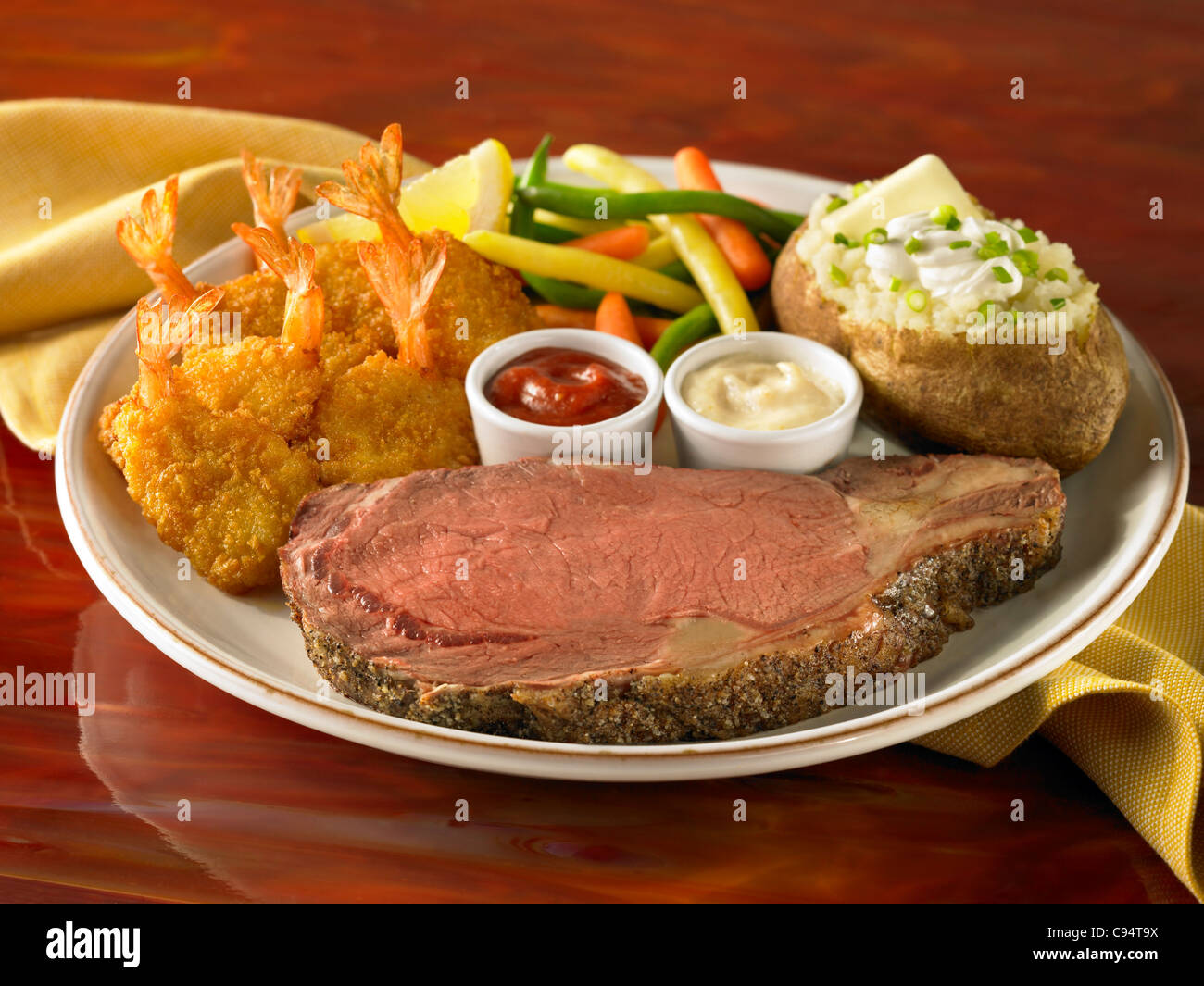 Prime Rib And Shrimp Dinner With Loaded Stuffed Potato And Vegetable Stock Photo
