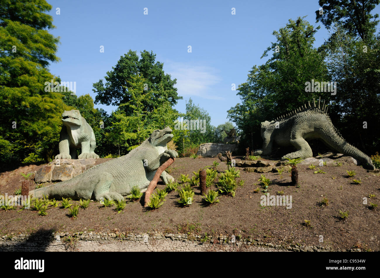 Dinosaur Statues Made Of Stone Amoungst Trees In Dinosaur Court At Crystal  Palace Park, South East London.