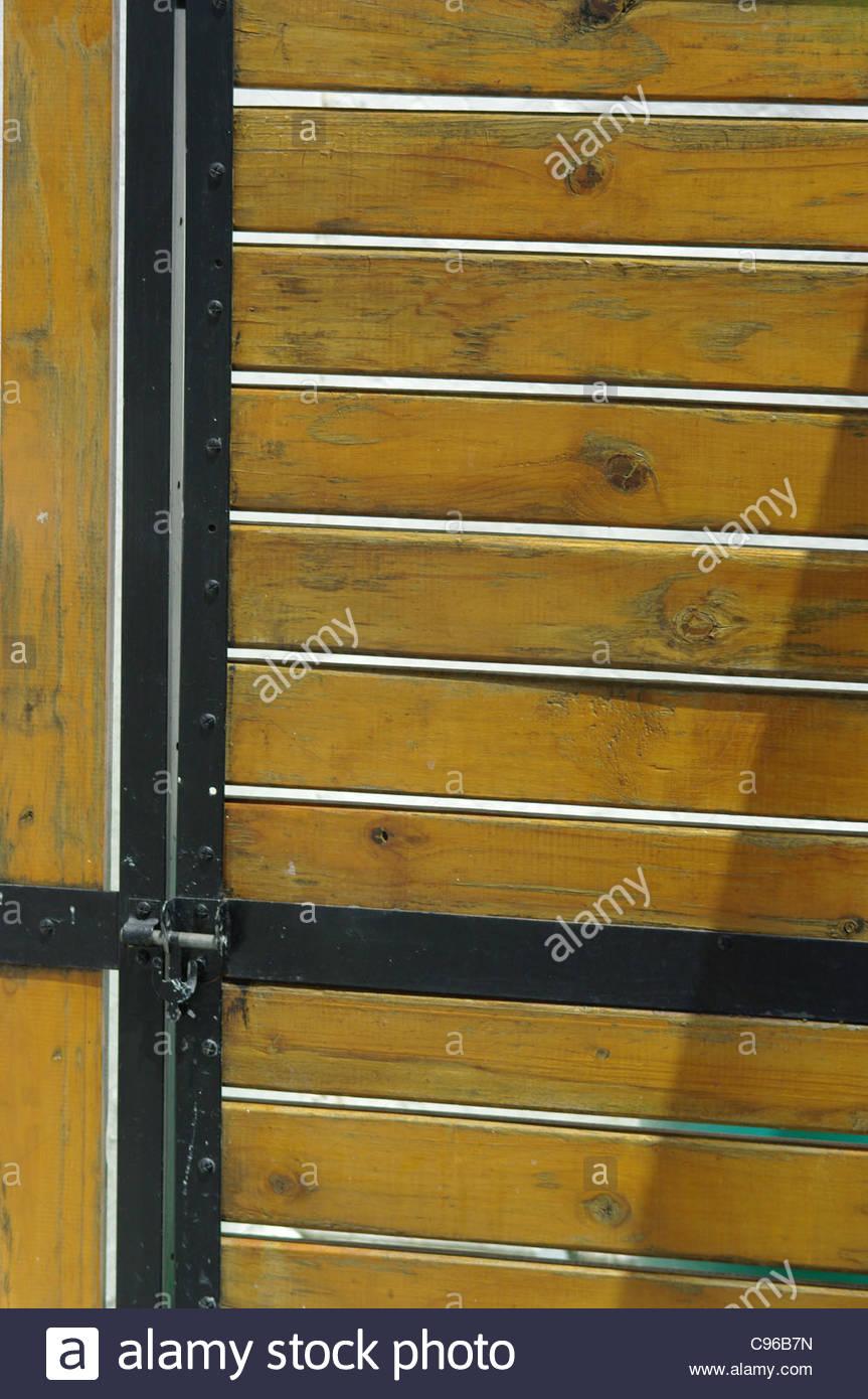 Stock Photo - Wooden security door with black metal trim WOOD SLATS gate varnished