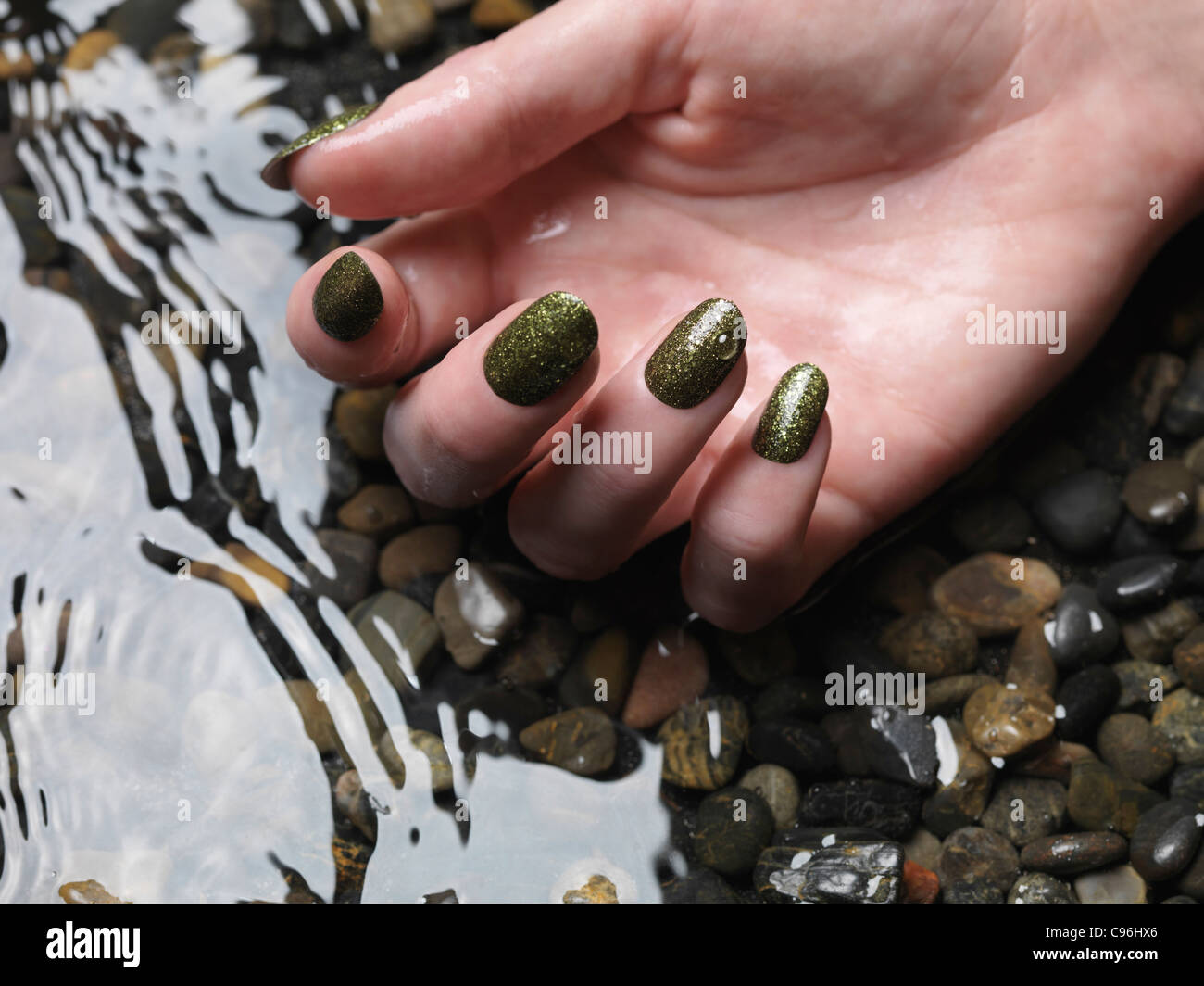 Closeup of woman hand with green fancy nail polish lying in water ...