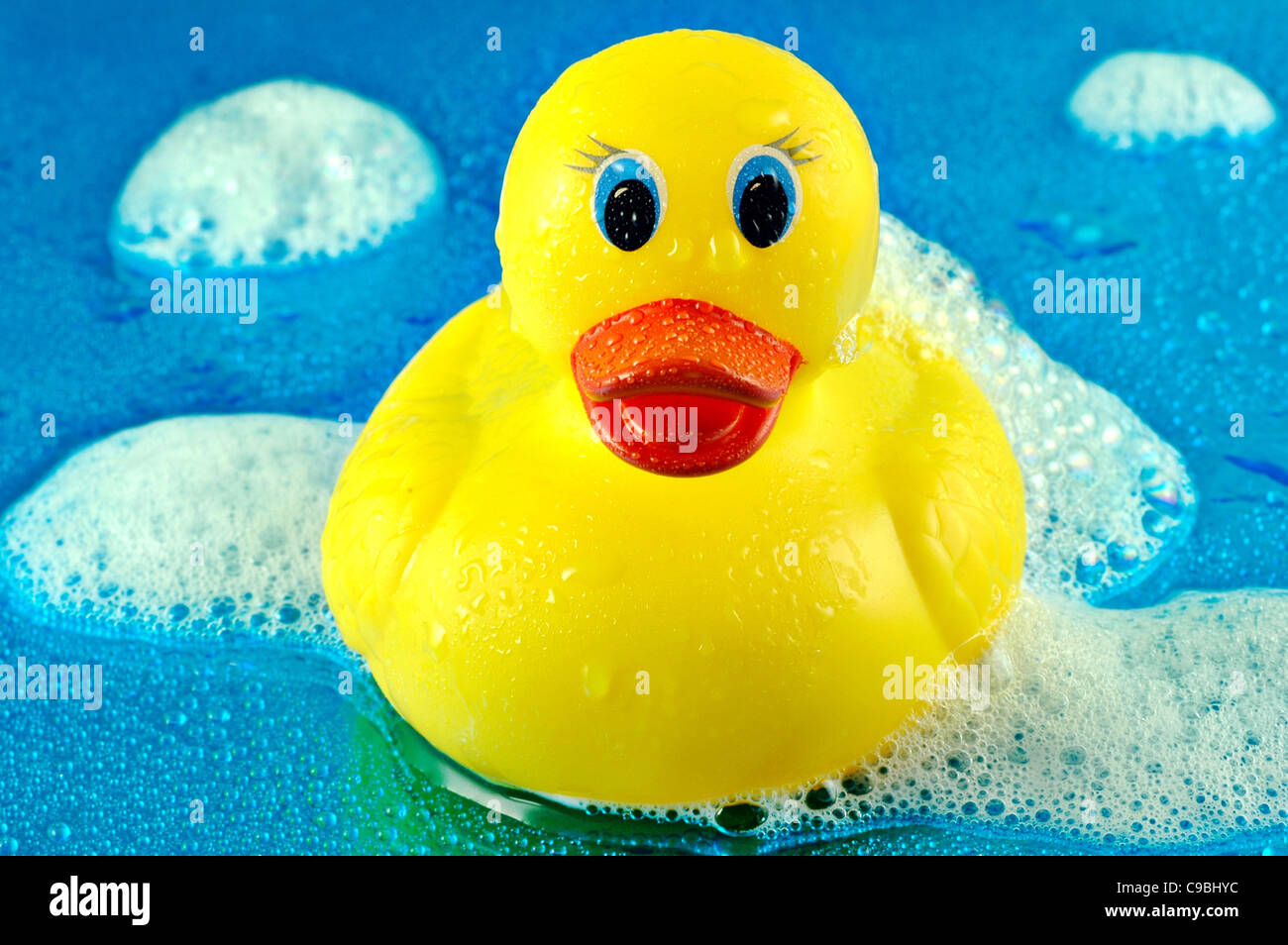 Toy Rubber Duck Swimming In Soap Bubbles On A Shiny Watery