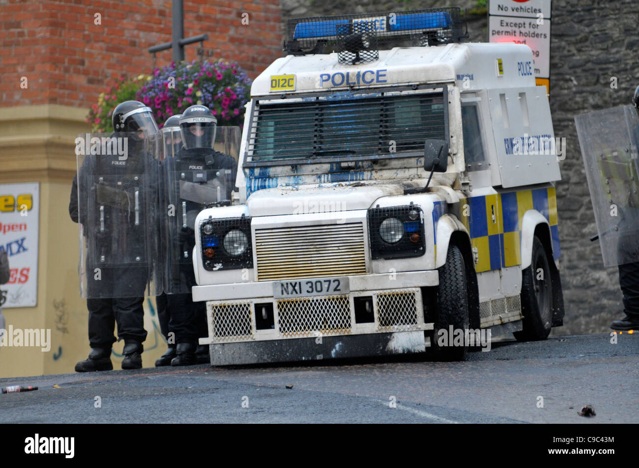 Psni Officers Beside An Armoured Land Rover During Riots