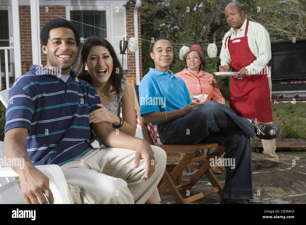 couple and family enjoying backyard barbeque stock