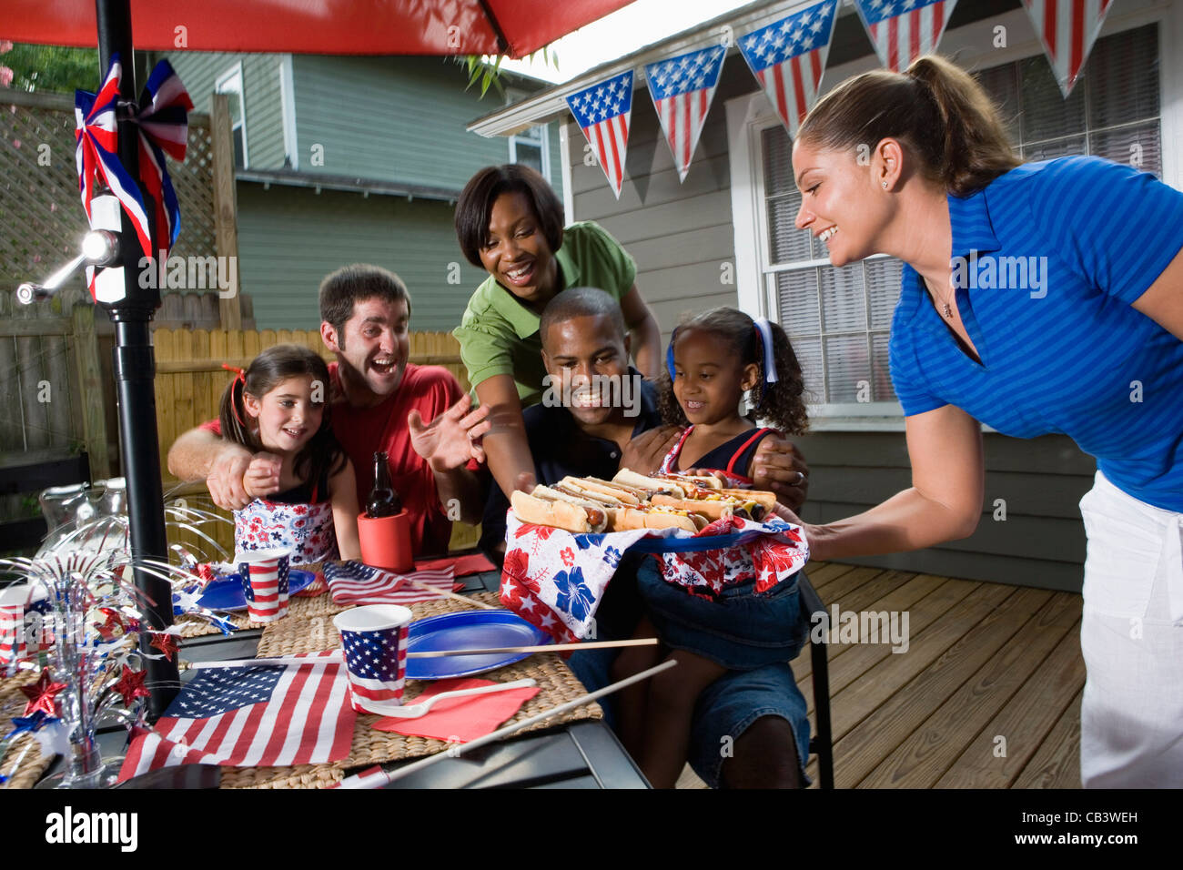 two families on backyard patio enjoying a cookout on the 4th of
