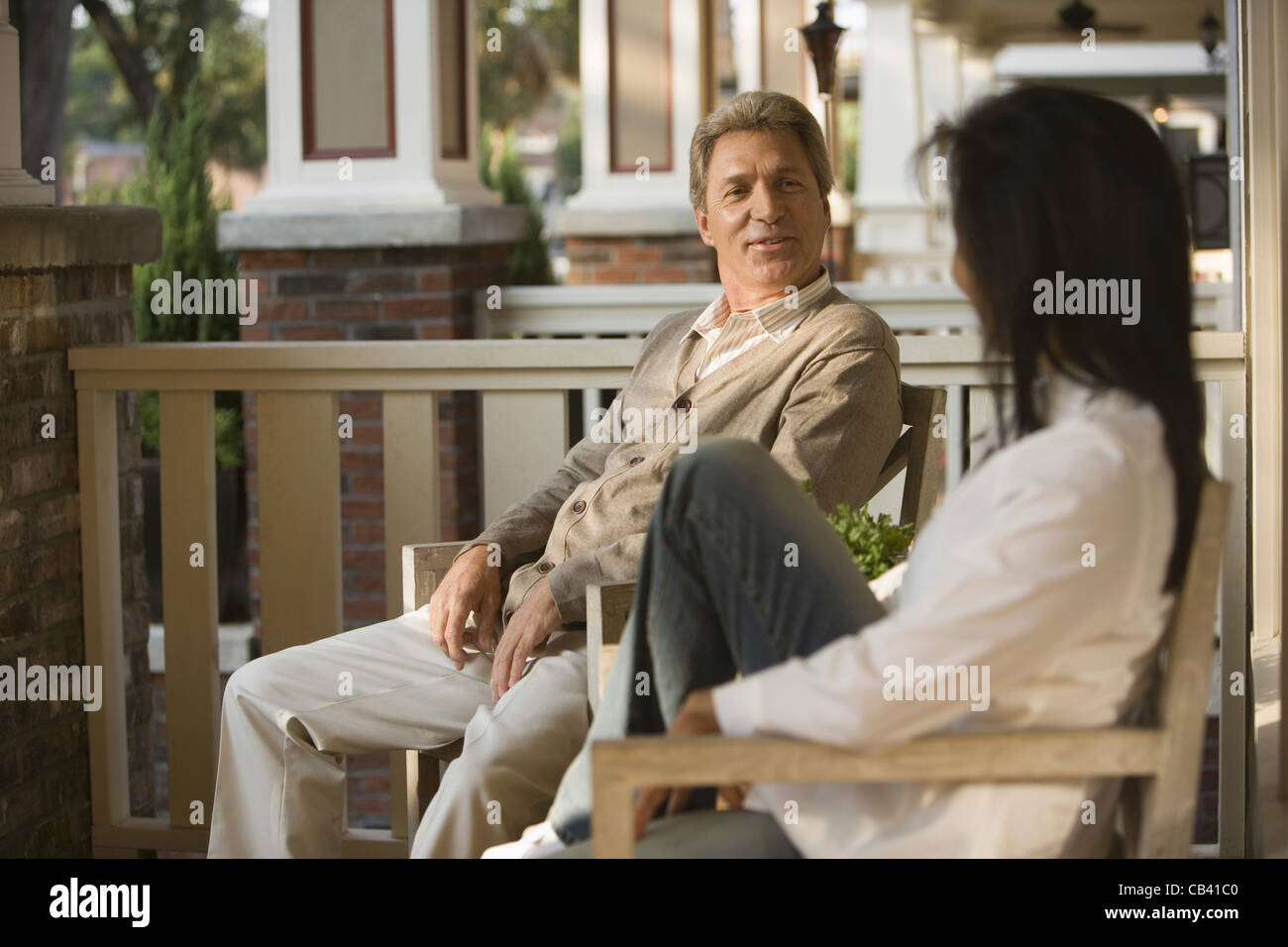 mature interracial couple sitting on front porch stock photo