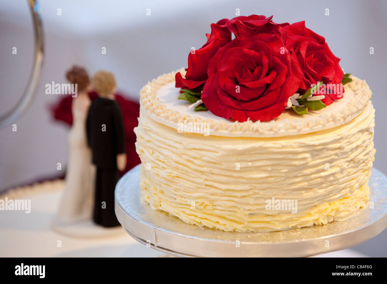 White Wedding Cake With Bride And Groom Figurines Red Roses