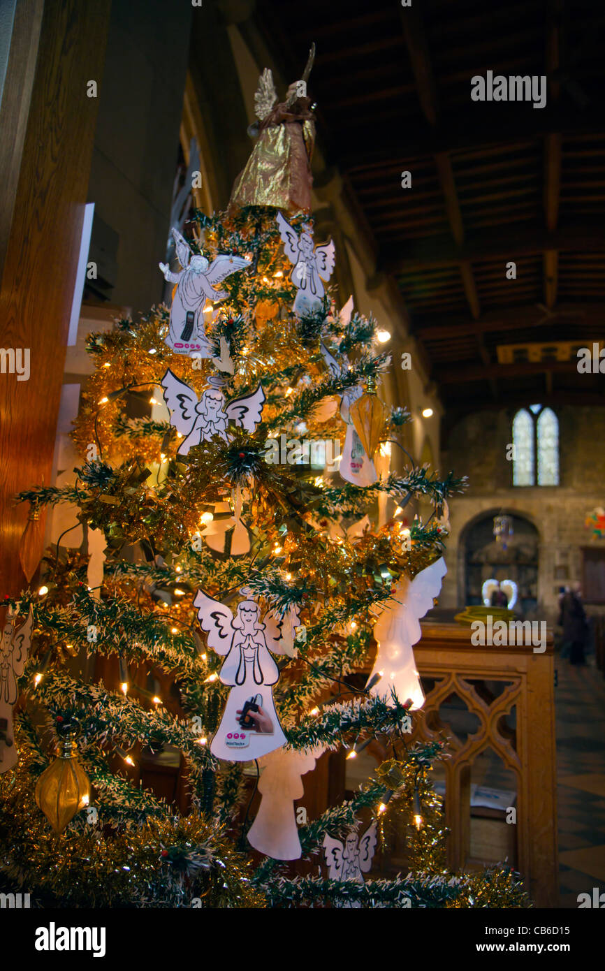 christmas tree decorated with angels and lights in a church