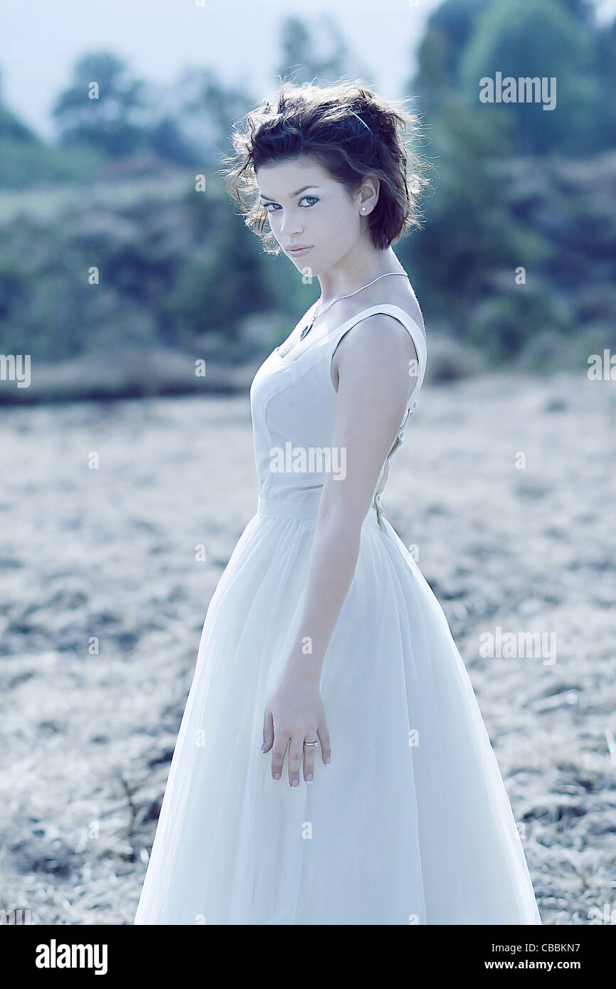 A young woman with short dark hair wearing a white wedding dress ...