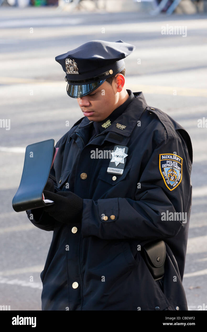 A nypd auxilliary police officer takes notes while on duty at a parade in new york