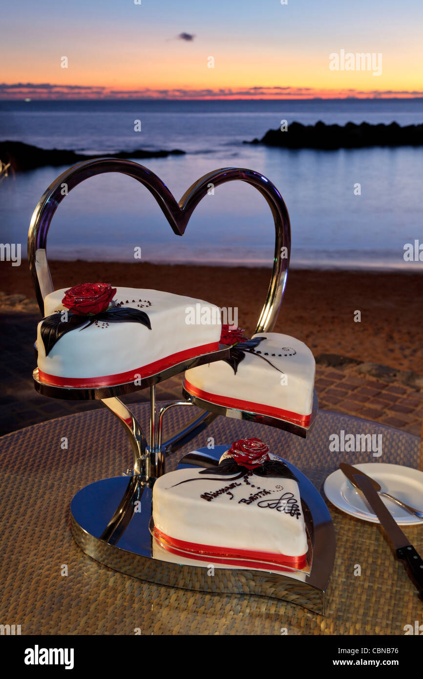 Three tiered wedding cake on a heart shaped cake stand at ...