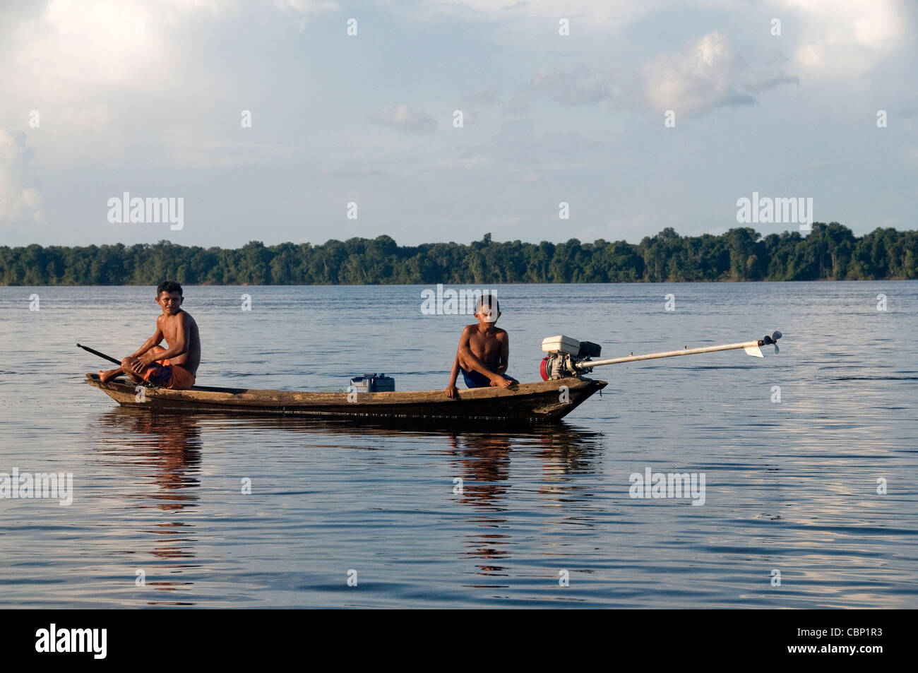 A couple of natives in a dugout canoe are fishing with for Amazon fishing net