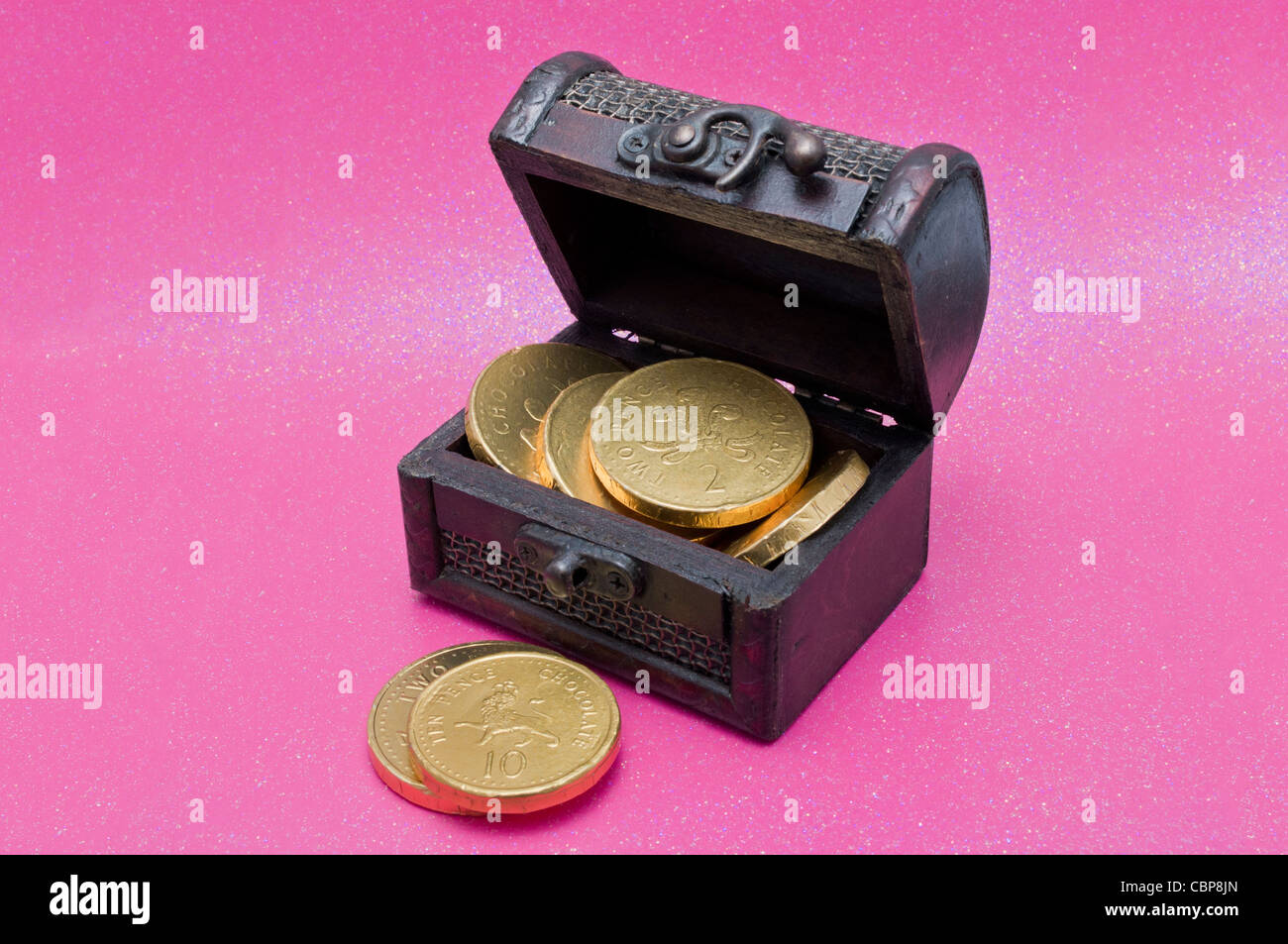 Treasure chest with gold chocolate coins on a sparkly pink ...