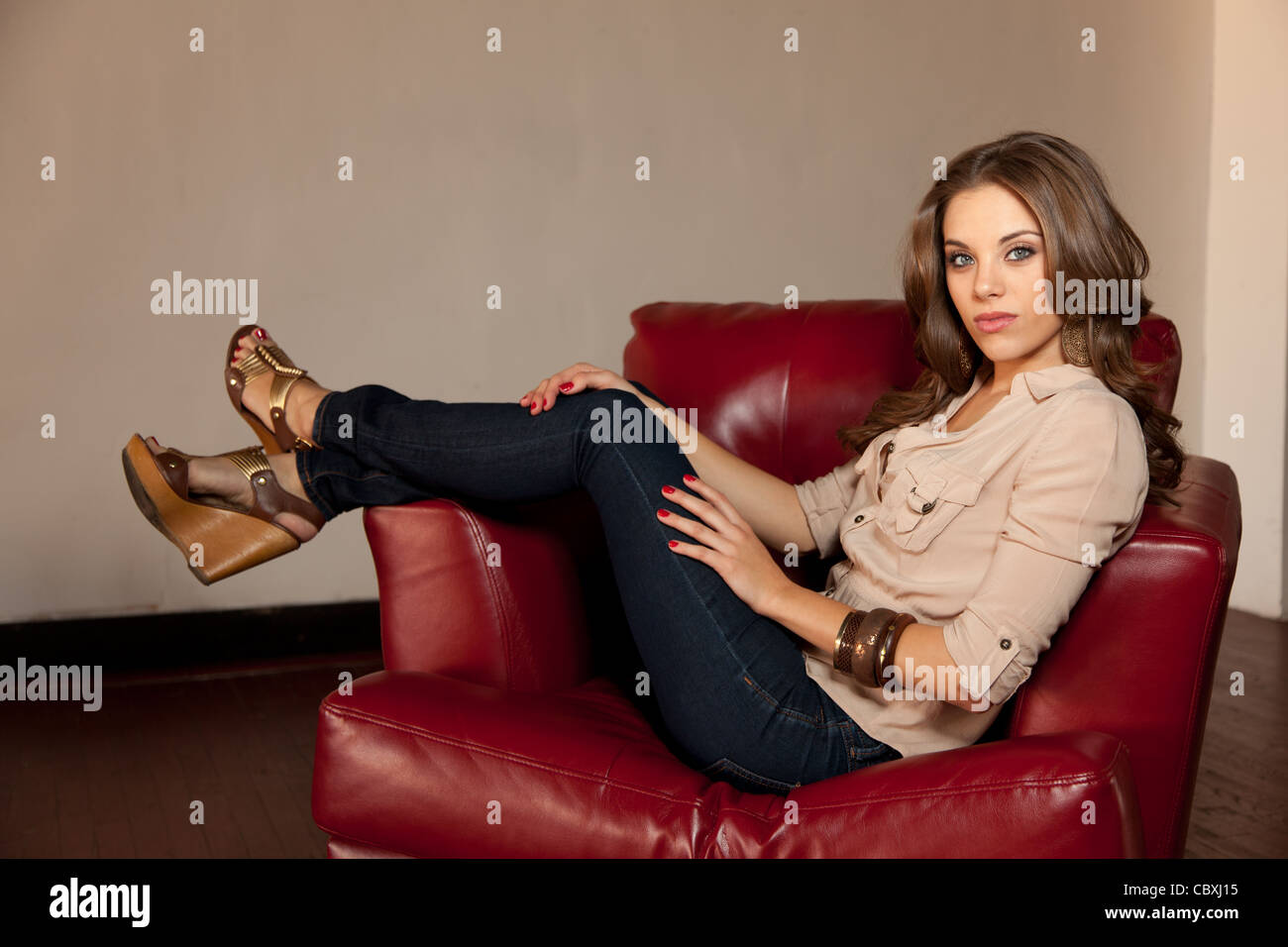 pretty caucasian woman sitting in a red leather chair stock photo