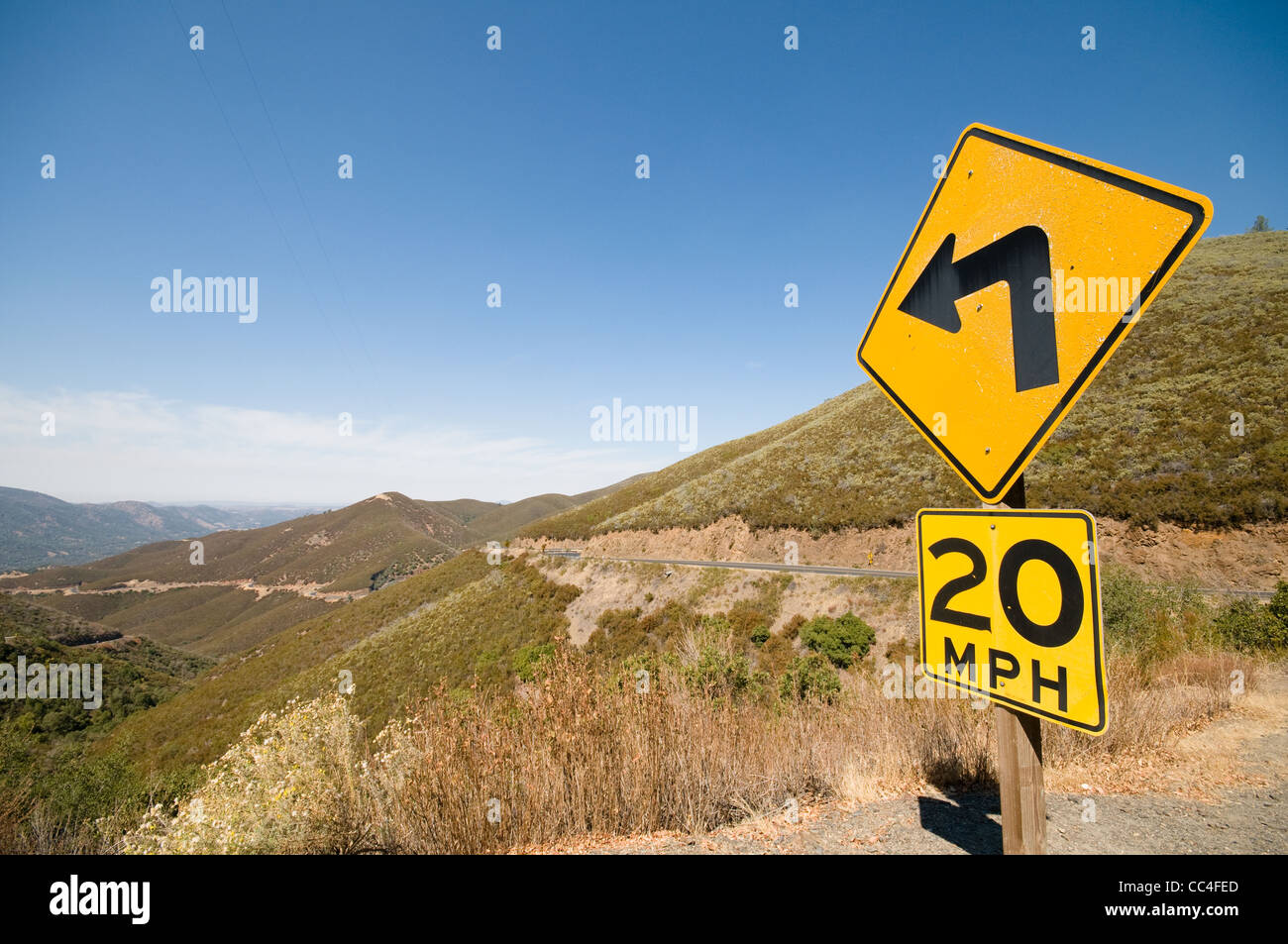Yellow road warning sign left turn 20mph with long winding road yellow road warning sign left turn 20mph with long winding road california publicscrutiny Images