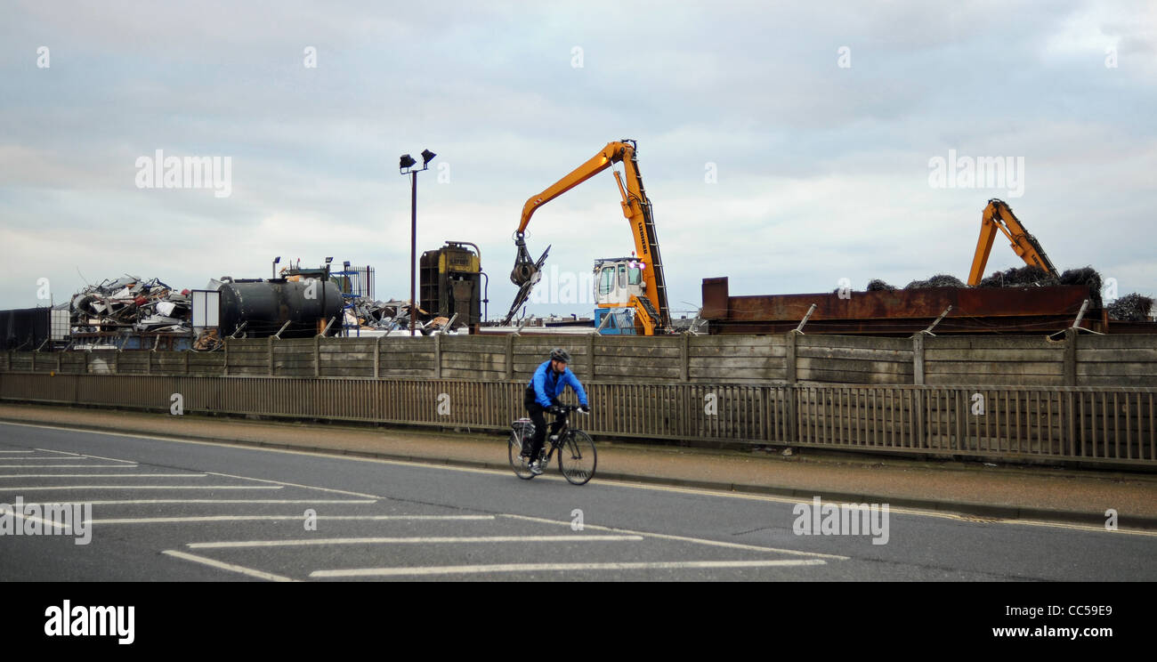 Cyclist rides past a scrap metal yard where old cars and vehicles ...