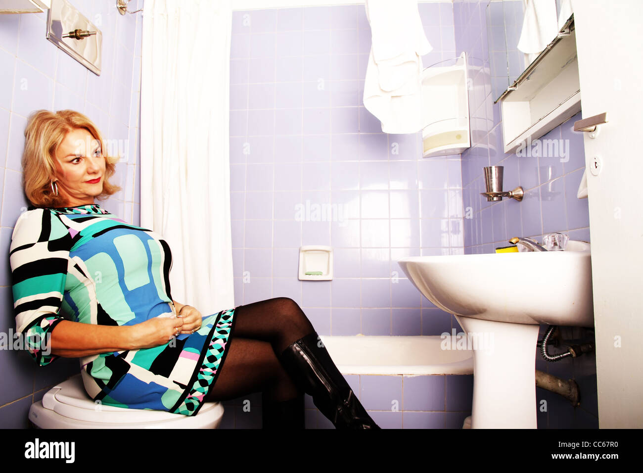 Desperate to use the bathroom - Vintage Femme Fatal Retro Shoot Woman Sitting On The Toilet Stock