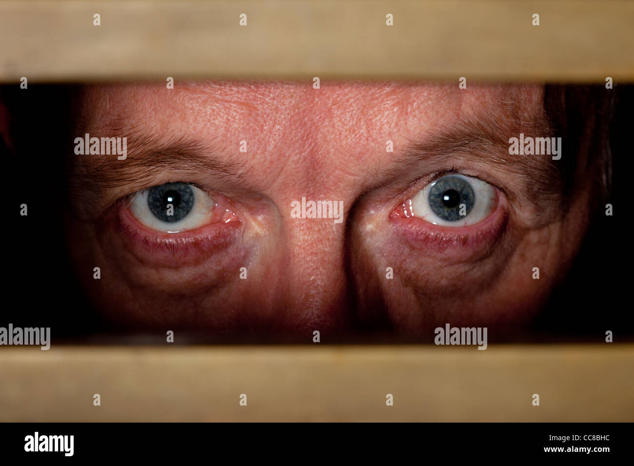 man-looking-through-letterbox-his-eyes-s