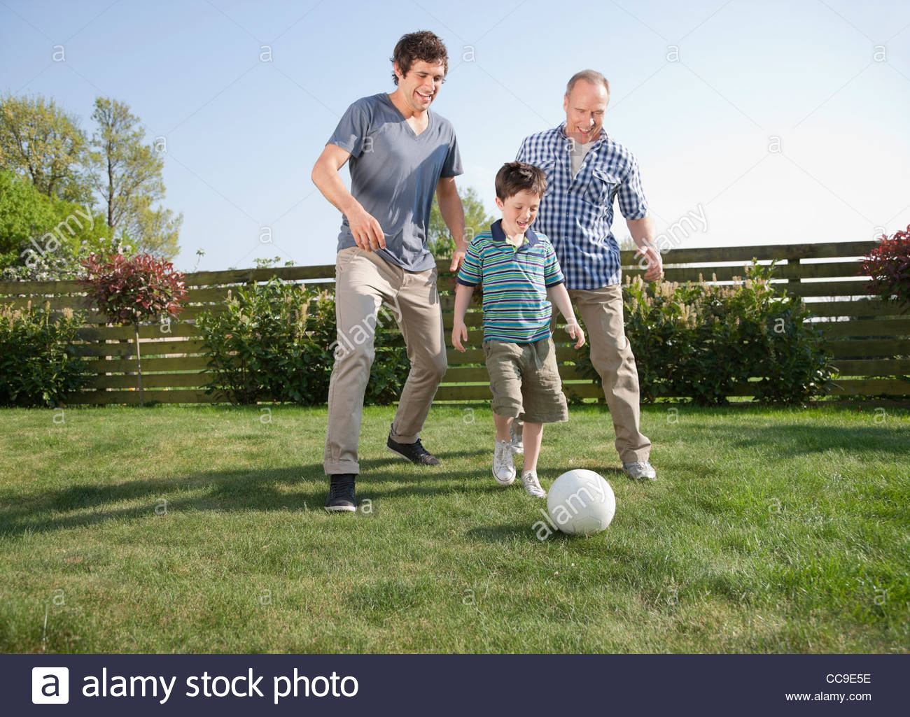 multi generation family playing soccer in backyard stock photo
