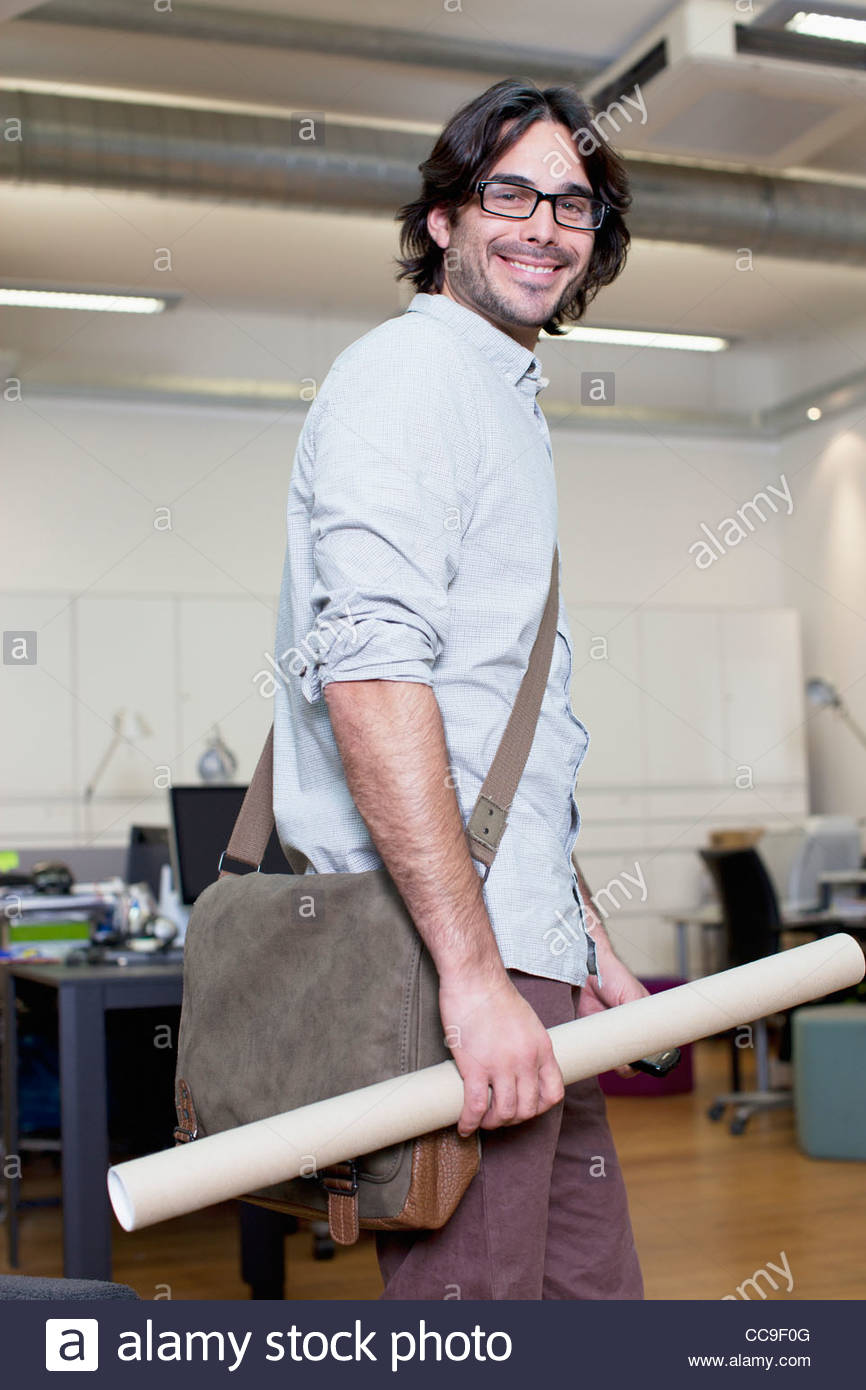Portrait of smiling architect holding blueprint tube in office stock portrait of smiling architect holding blueprint tube in office malvernweather Image collections