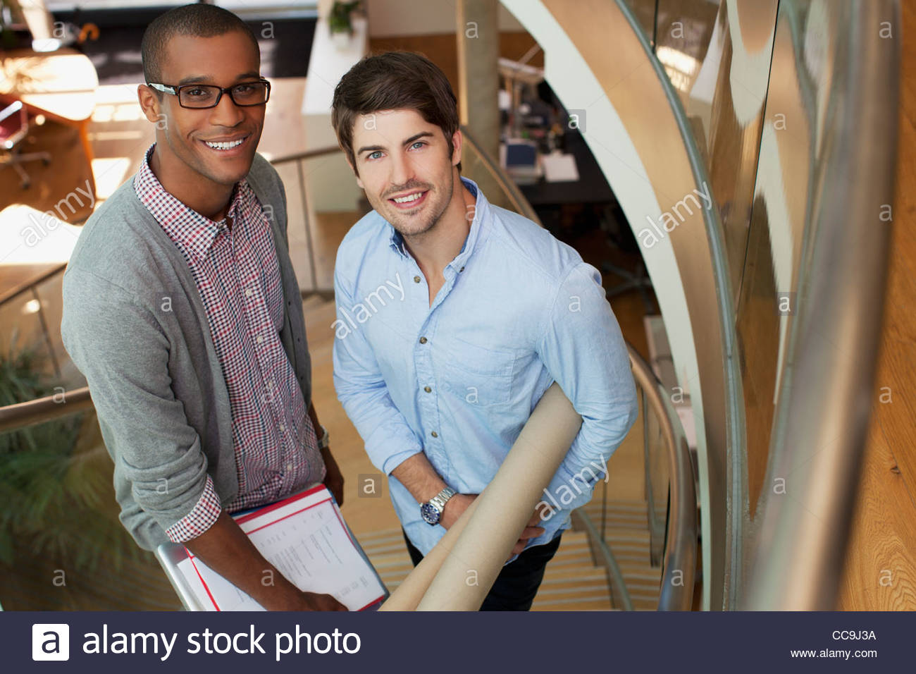 Portrait of smiling architects with blueprint tubes on stairs in portrait of smiling architects with blueprint tubes on stairs in office malvernweather Image collections