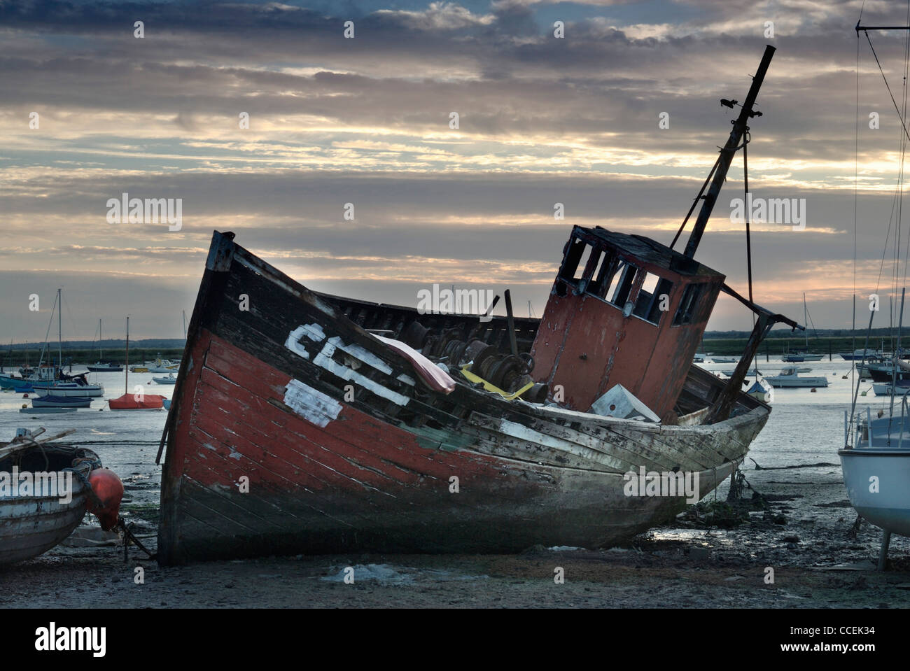 Fishing boat at low tide at sunset mersea island essex for Tide for fishing