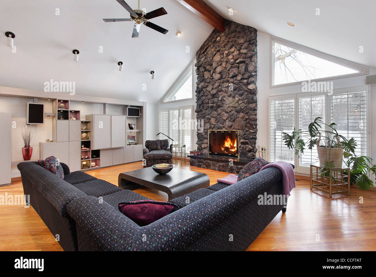 family room with two story stone fireplace and wood beams stock