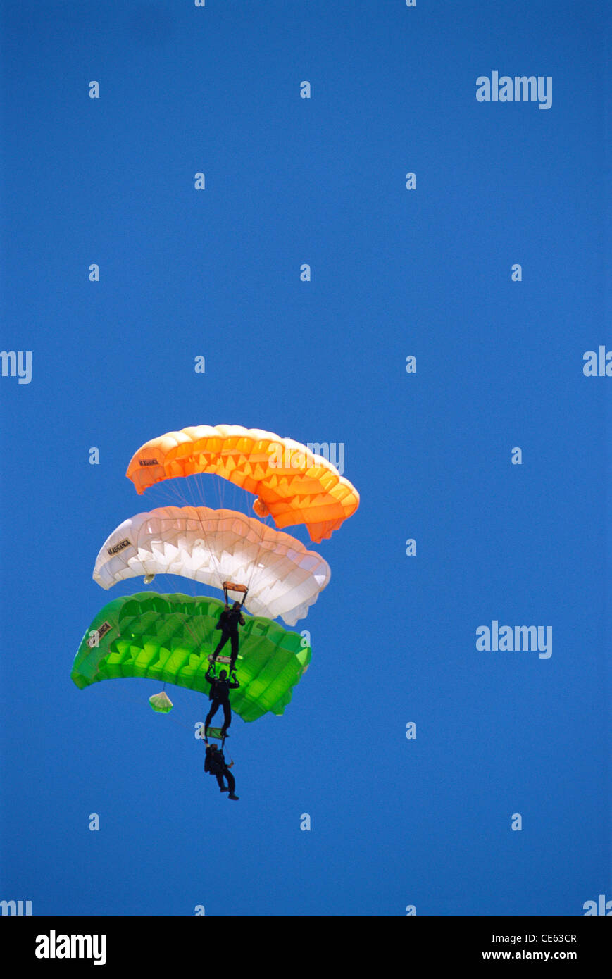 three men paragliding with parachutes of colours of indian flag