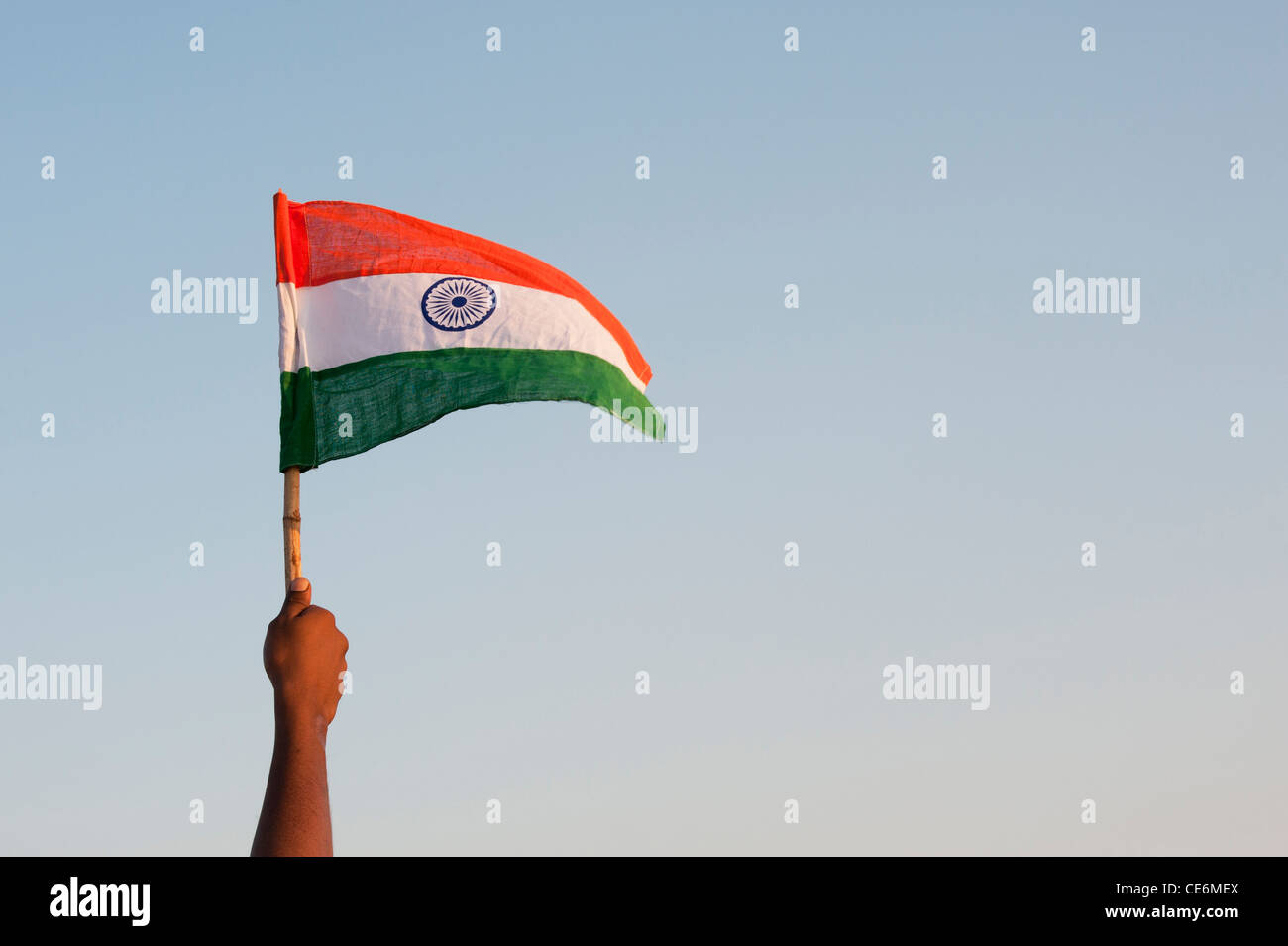 indian mans hands holding an indian flag against a blue sky india