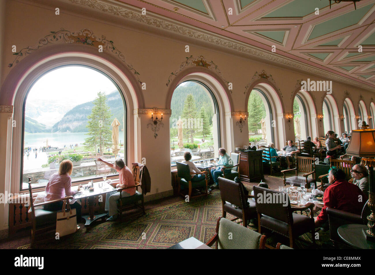 people viewing lake louise from the restaurant inside the fairmont