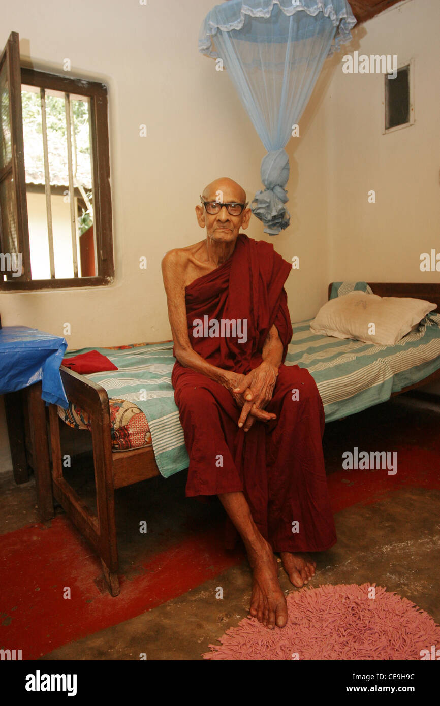 A Elderly Buddhist Monk Sits On The Side Of His Bed In His