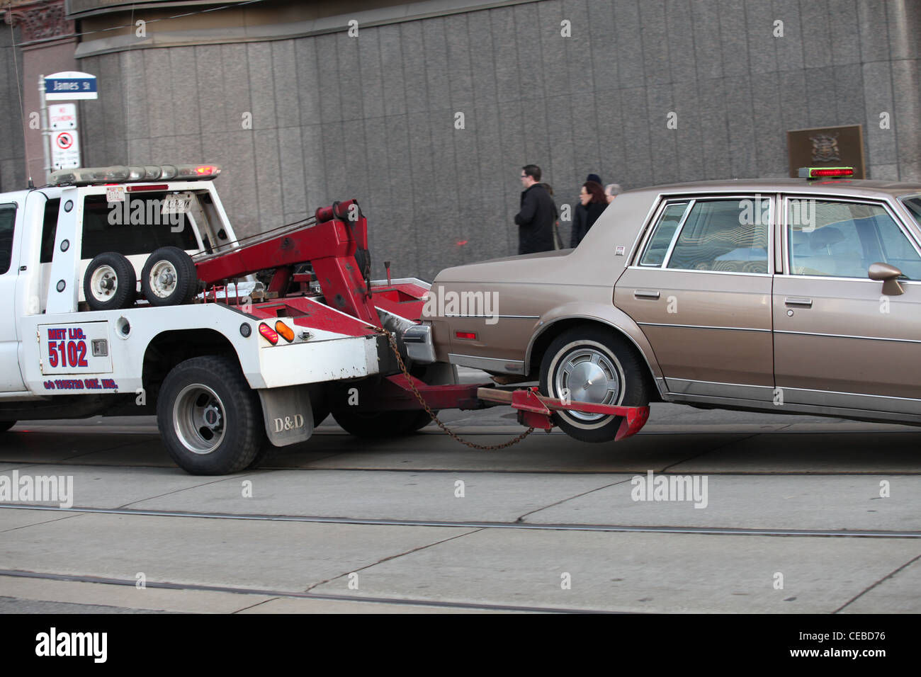 Tow truck hauling a car on street in downtown toronto canada stock image