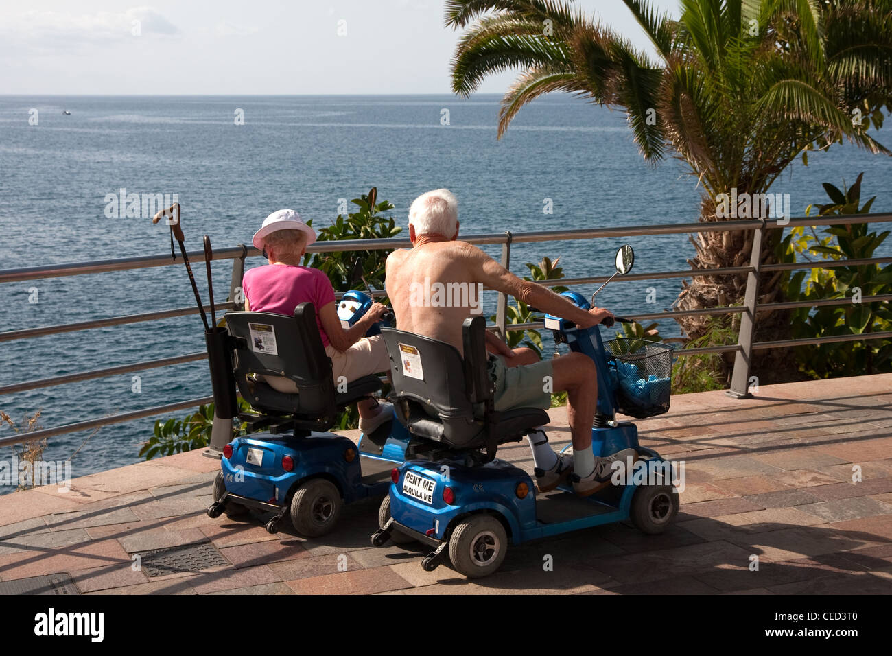 Elderly couple on mobility scooters looking out to sea for Motorized cart for seniors