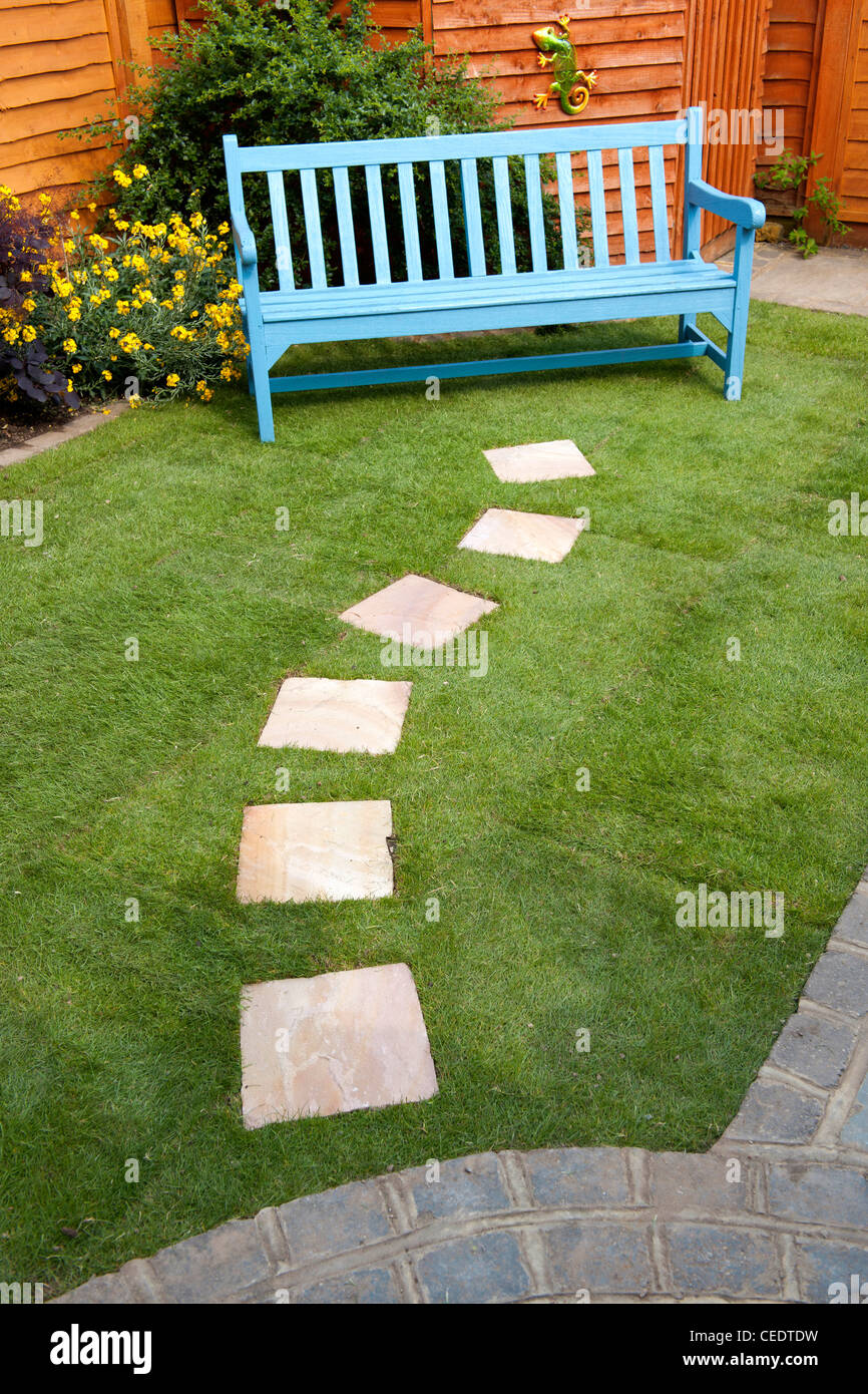 Small Garden With Stepping Stones Leading To A Bench