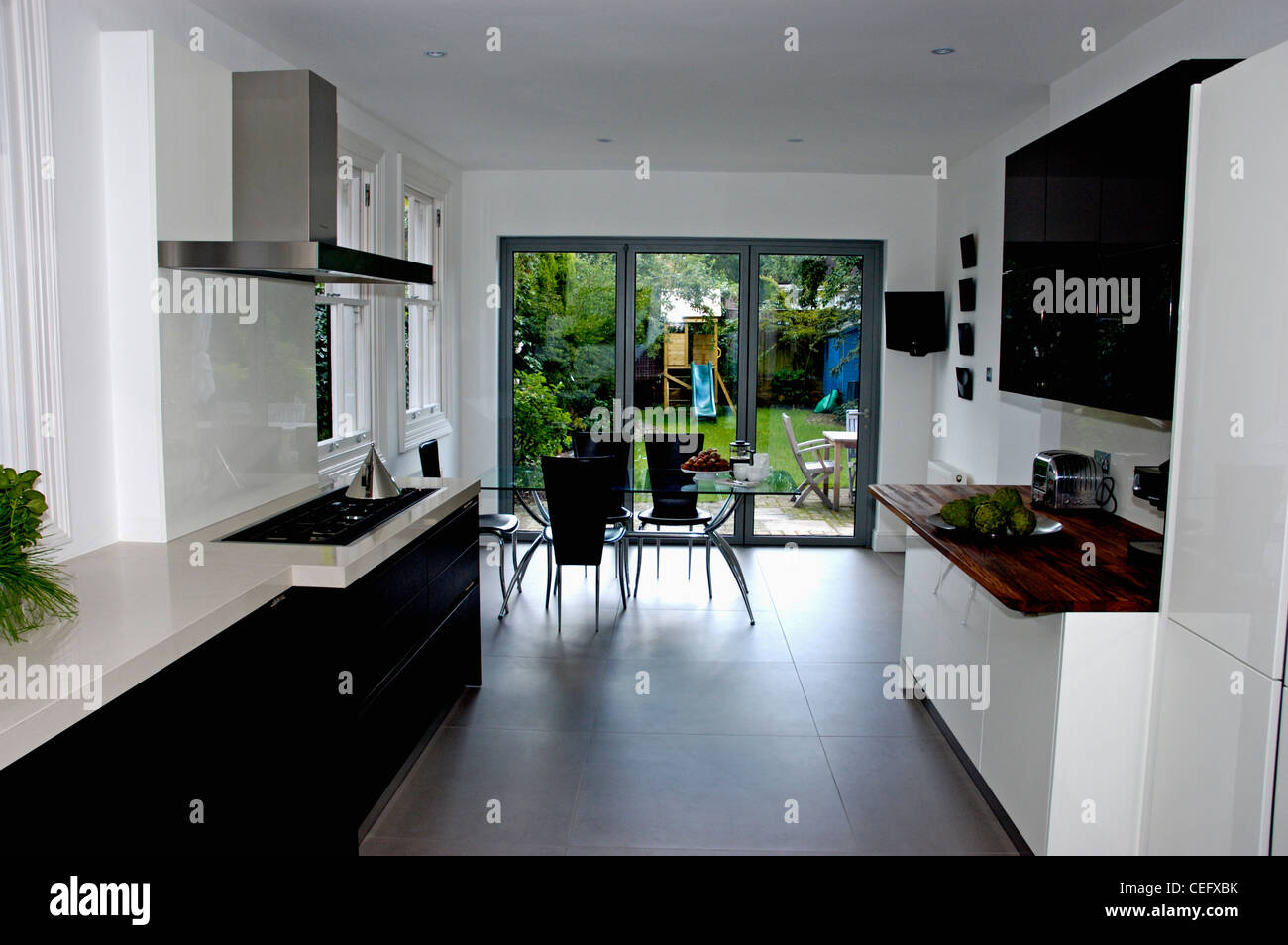 Modern White Kitchen Dining Room With Black Flooring And Glass Patio Doors To The Garden