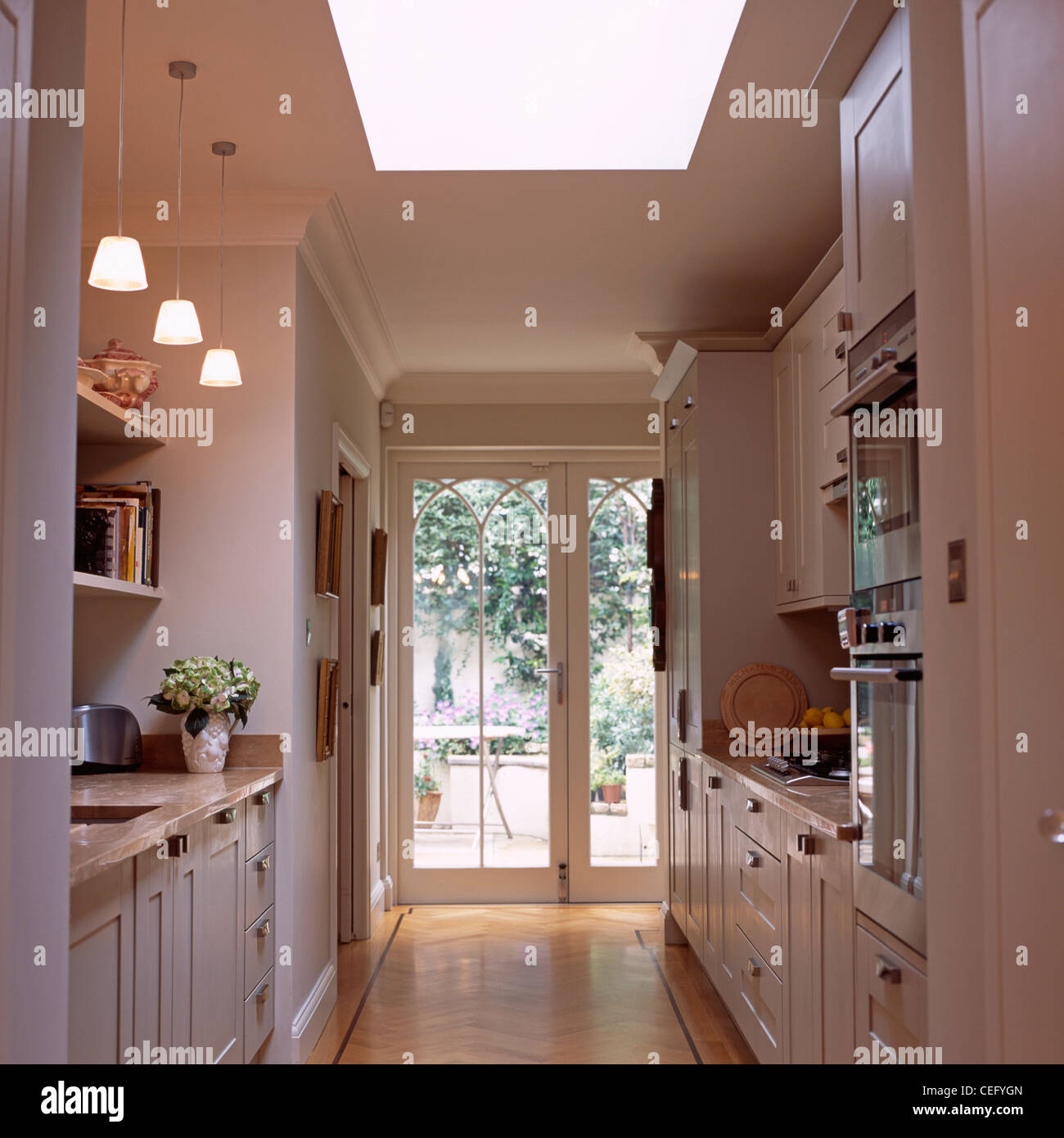 Pendant lights above worktop in white galley kitchen extension ...