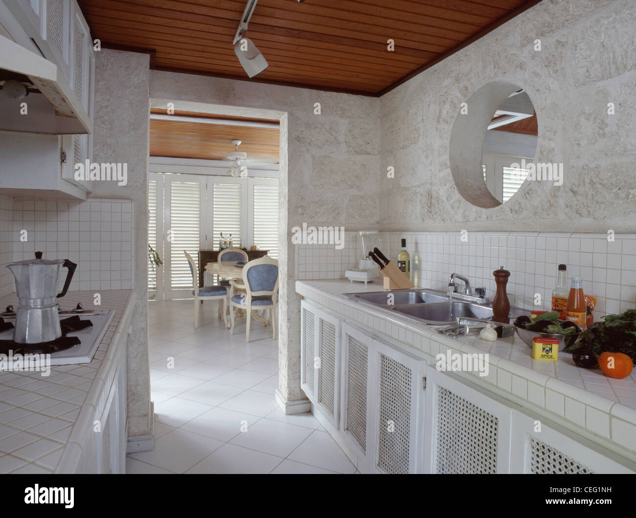 Circular internal window above sink in modern galley kitchen with circular internal window above sink in modern galley kitchen with white ceramic floor tiles and view of dining room dailygadgetfo Image collections