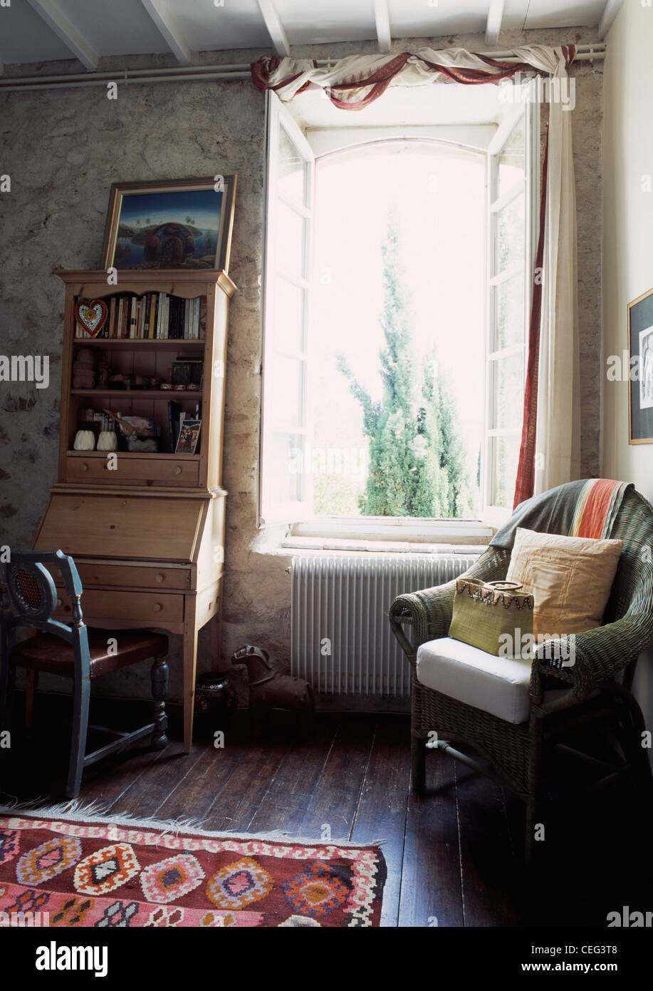 cushions on green wicker chair beside window in french country cushions on green wicker chair beside window in french country living room with antique pine desk and stone walls