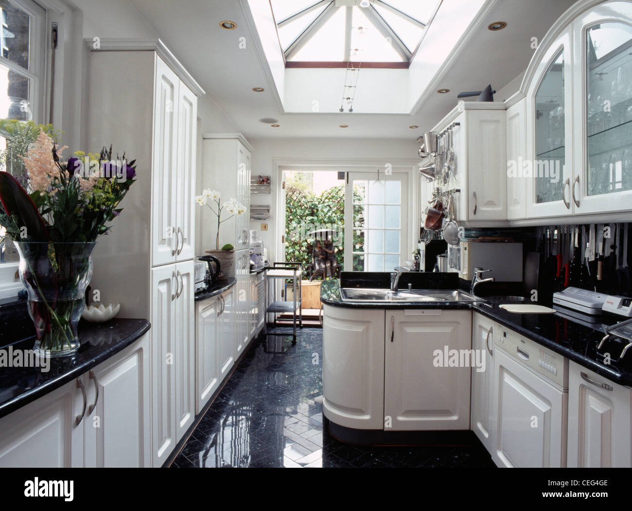 White Kitchen Units Black Worktop large skylight in modern kitchen extension with fitted white units