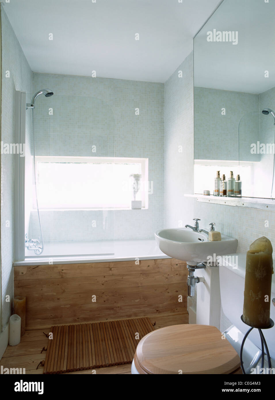 Shower Above Wood Paneled Bath In Modern White Bathroom With Large Mirror Basin