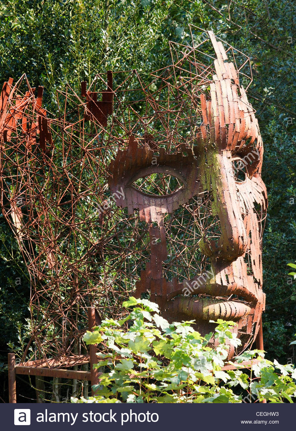 Rusted Steel Vertical Face Sculpture Amongst Trees In The Sculpture Garden,  Burghley House, Stamford, Lincolnshire, England, UK
