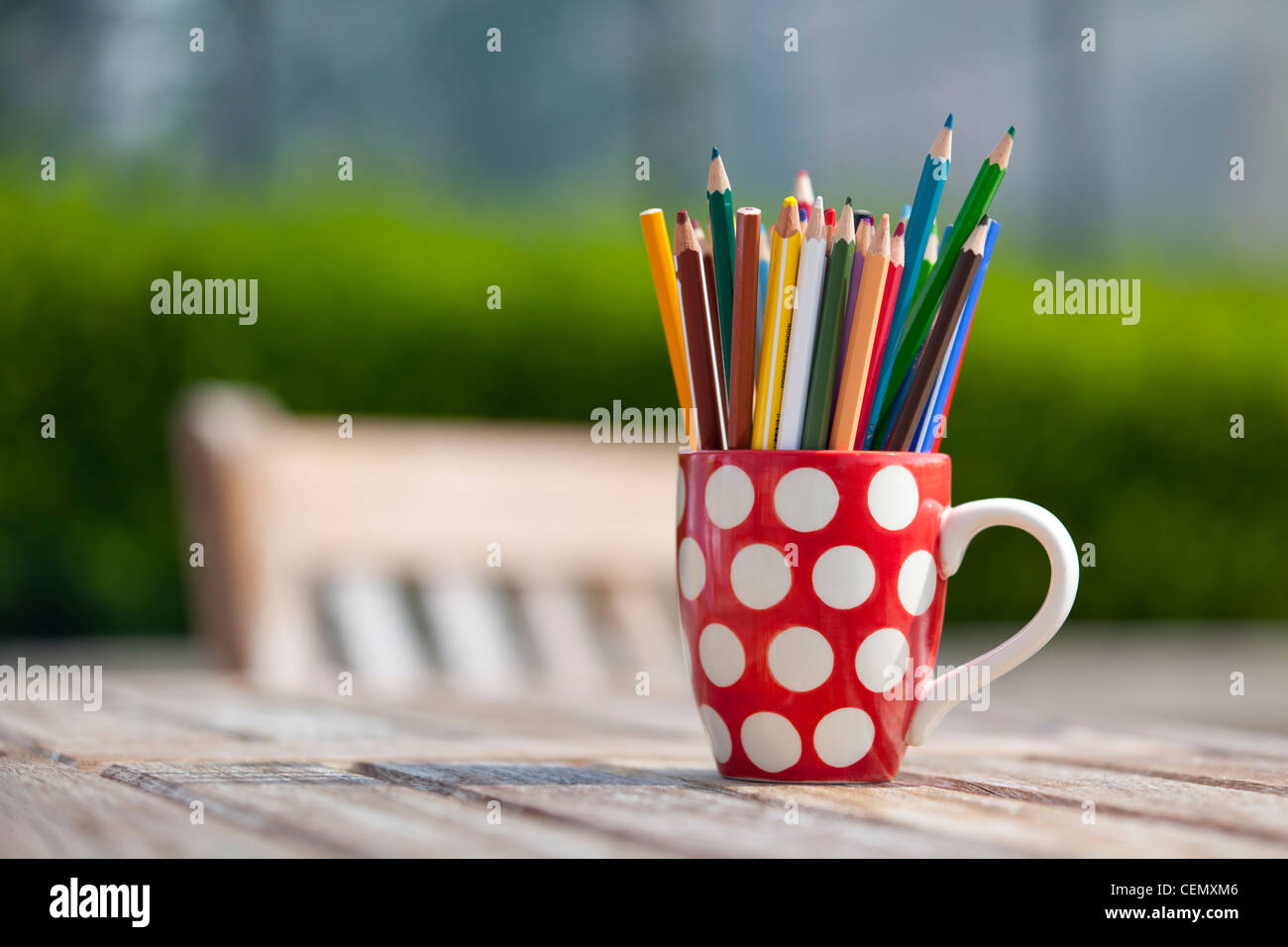 coloring colouring pencils in a red and white polka dot mug outside ...