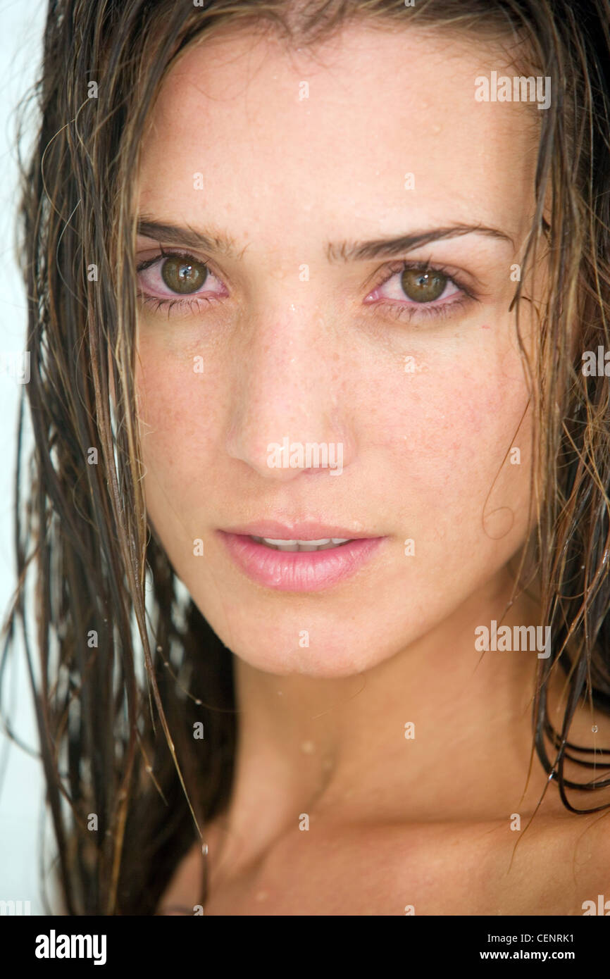 close up of female with long wet brunette hair looking to camera