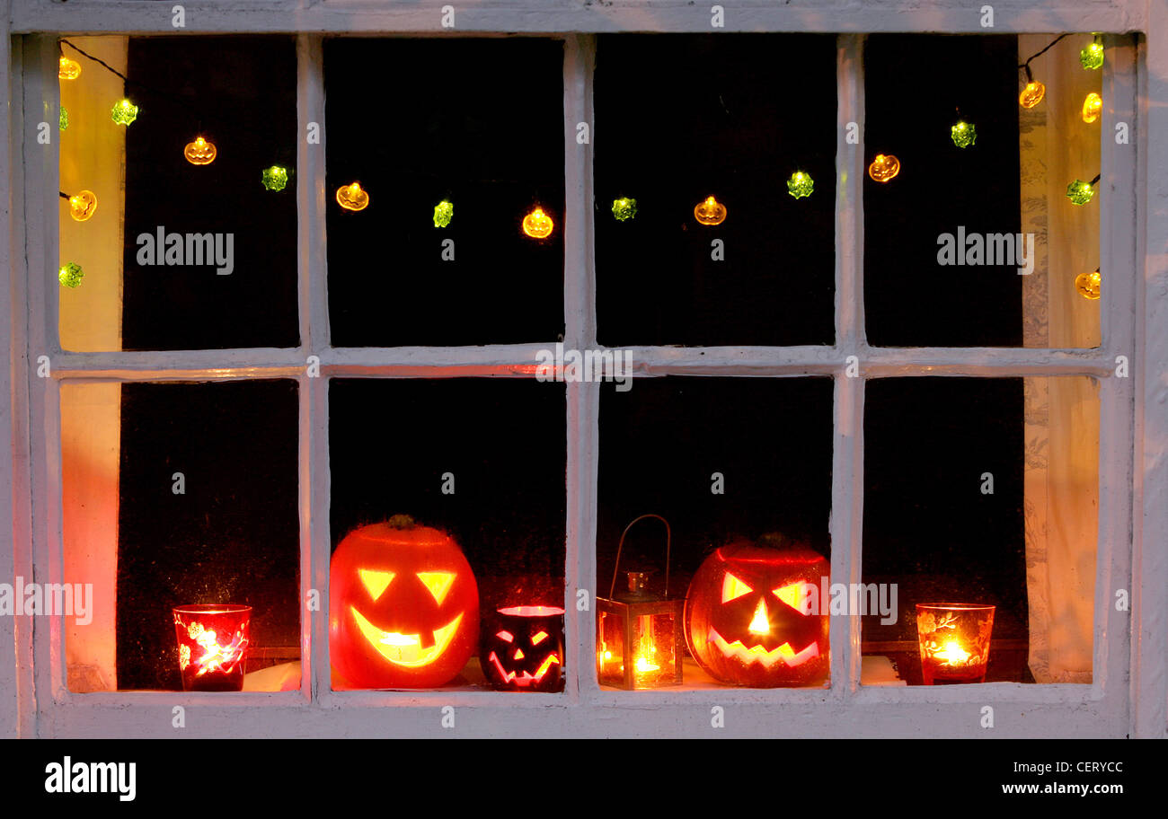 Carved Halloween pumpkins, a lantern and candles in orange and red glasses  on a window sill Halloween fairy lights hanging up, - Carved Halloween Pumpkins, A Lantern And Candles In Orange And Red
