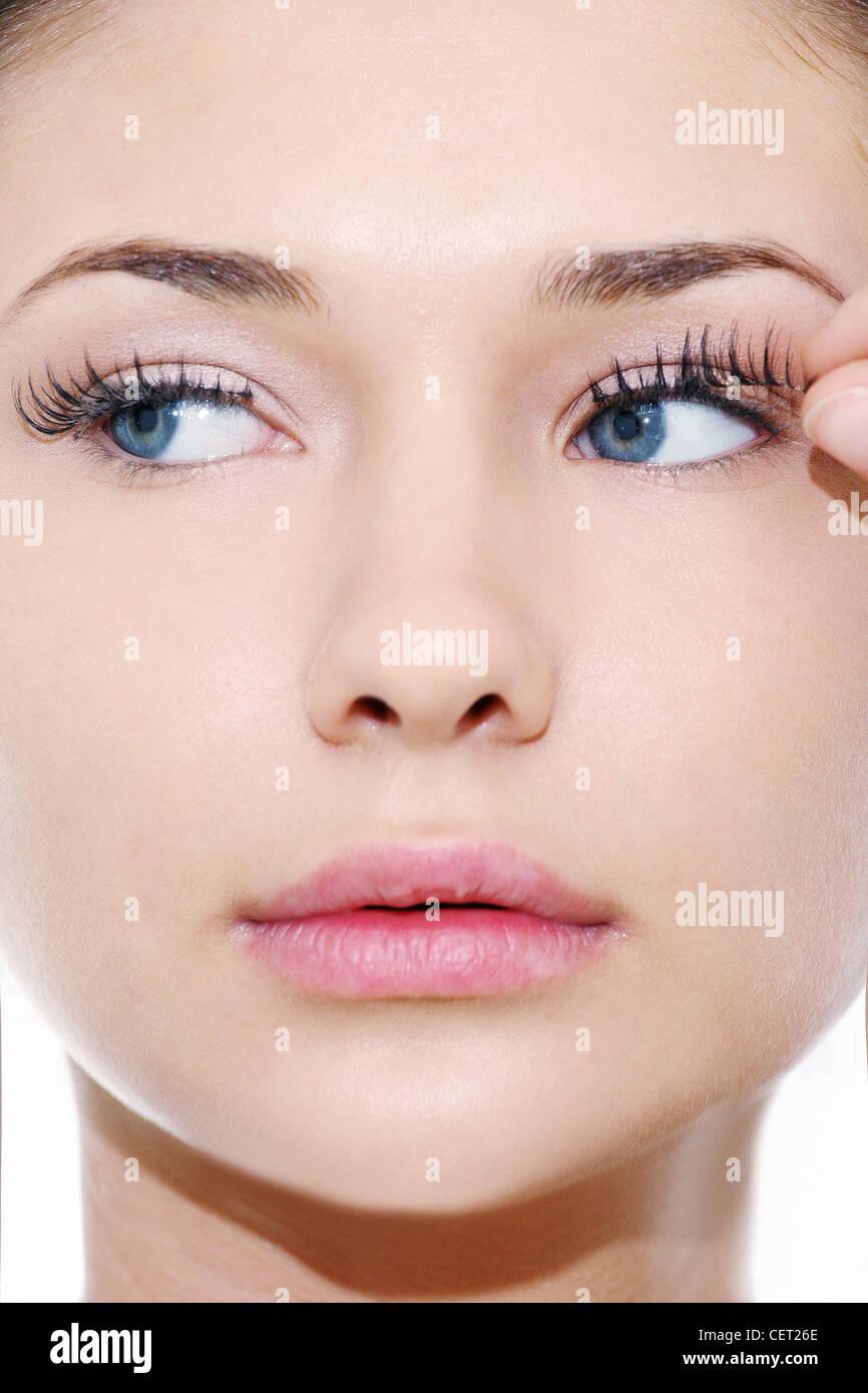 Female with blue eyes applying false eyelashes ANDREA CIRIMINNA ...