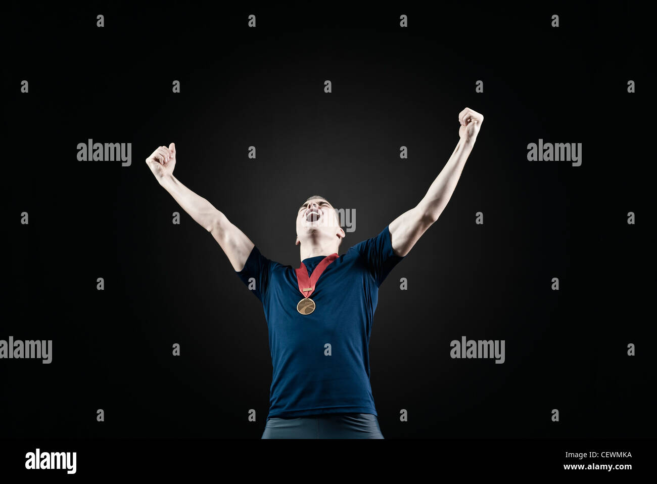 Male Athlete With Arms Raised In Victory Stock Photo