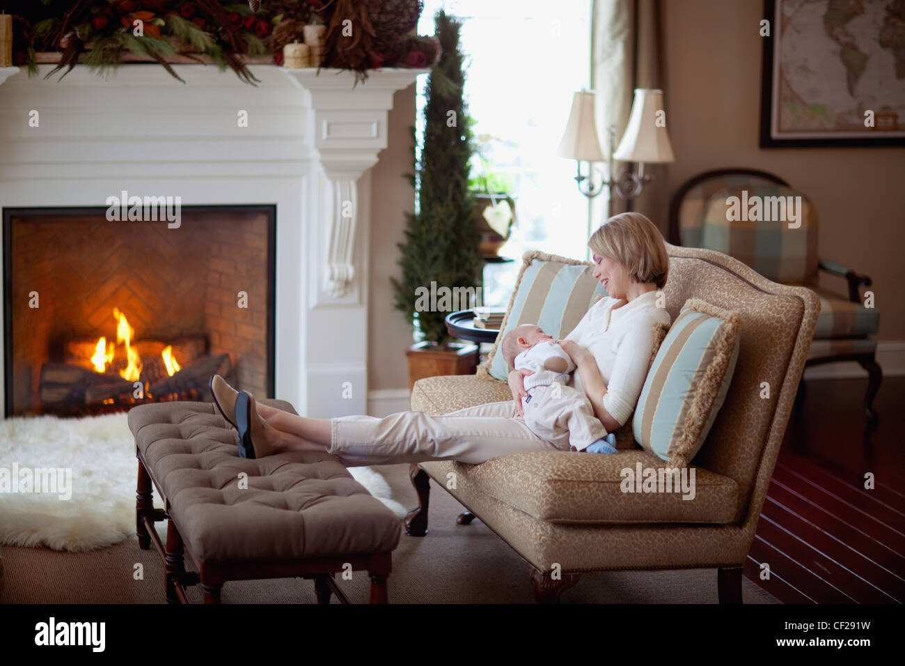A Mother Holding Her Baby By A Fireplace In The Living Room ...