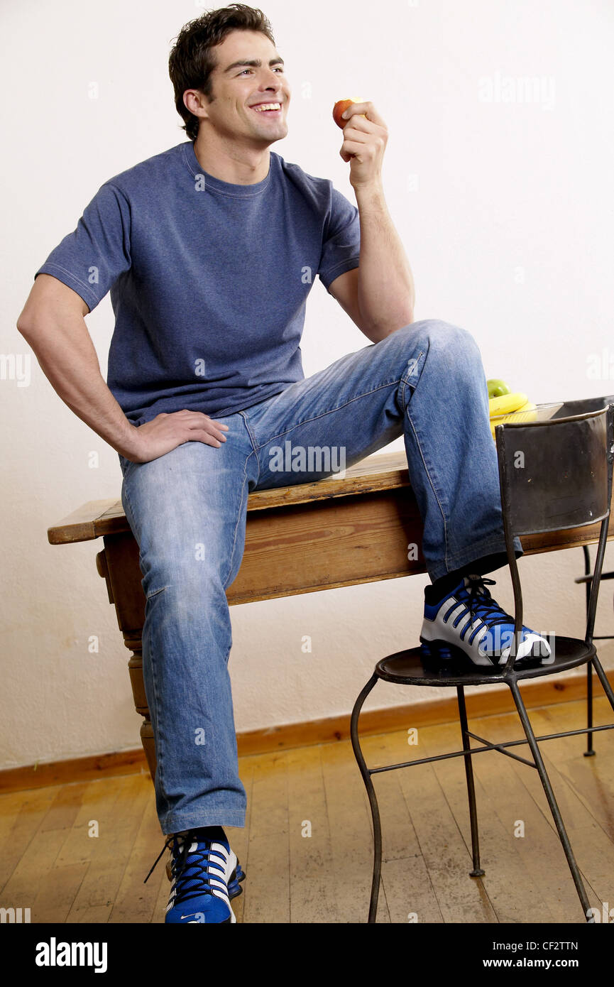 Black t shirt blue jeans - Male Dark Brown Hair Wearing Blue T Shirt Faded Blue Jeans And Blue White And Black Trainers Sitting On Wood Dining Table