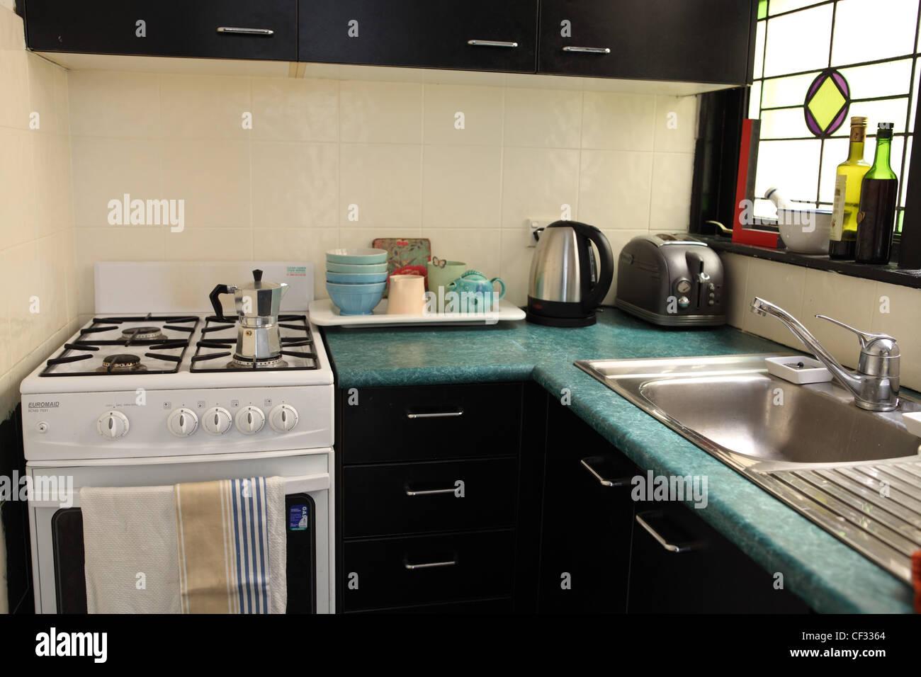 stock photo sydney apartment kitchen interiwith black kitchen units green worktops stainless steel kitchen sink free standing white - Kitchen Sinks Sydney