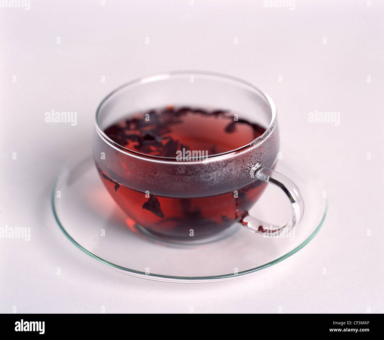 See Through Glass Hibiscus Tea With Tea Leaves Floating In A See Through Glass Cup